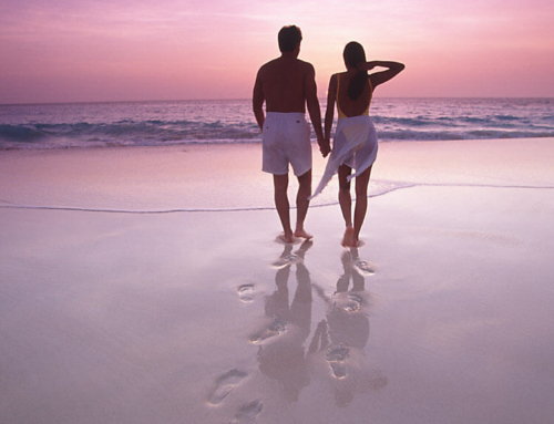Couple-walk-on-beach-hand-in-hand-towards-Aruba-sunset